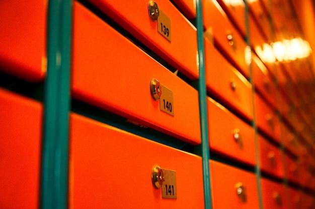 Boîtes aux lettres orange dans un immeuble résidentiel. même rangées de boîtes aux lettres numérotées. concept de correspondance en ville. vous pouvez l'utiliser comme arrière-plan pour votre création. espace de copie