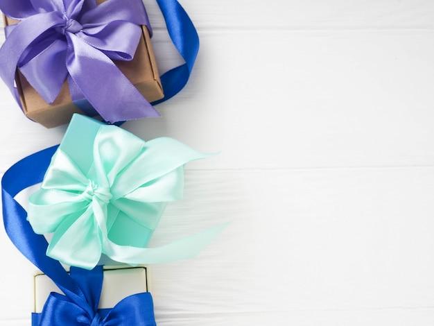 Boîtes bleues avec des arcs pourpres, cadeaux de noël sur fond blanc, espace de copie