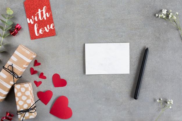 Boîtes de cadeau près des cœurs en papier, feuille, stylo et étiquette