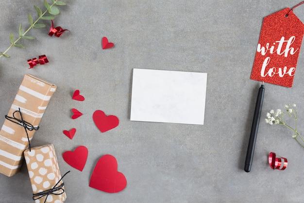 Boîtes de cadeau près des coeurs en papier, des feuilles, des stylos et des étiquettes