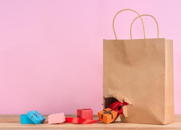Des boîtes à cadeaux colorées tombent du sac en papier