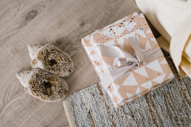 Des boîtes à cadeaux de noël ou du nouvel an sont sur le sol, à côté desquelles se trouvent des chaussons pour enfants en forme de hérisson