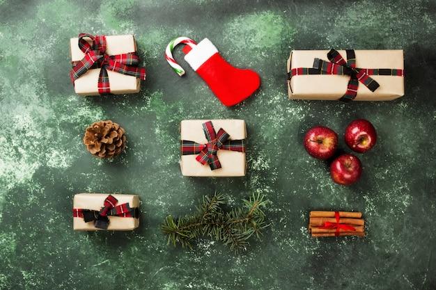 Boîtes avec des cadeaux pour noël et bas avec une canne en bonbon sur fond gris, vue de dessus