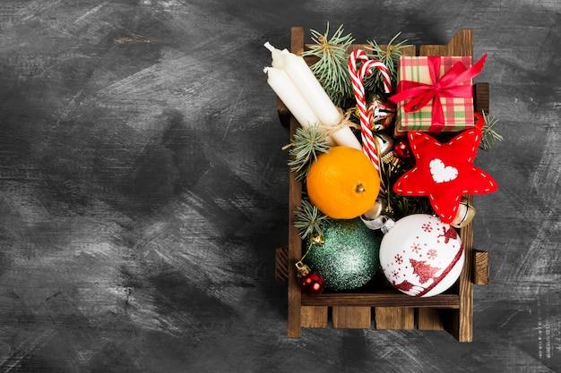 Boîtes avec des cadeaux pour noël et divers attributs de vacances sur une surface sombre