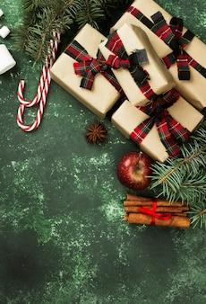 Boîtes avec des cadeaux pour noël et divers attributs de vacances sur une surface verte