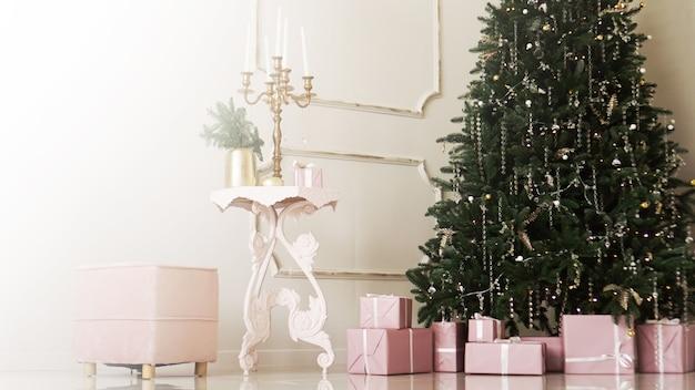 Boîtes cadeaux roses avec des rubans sous le sapin de noël dans des appartements classiques à l'intérieur blanc