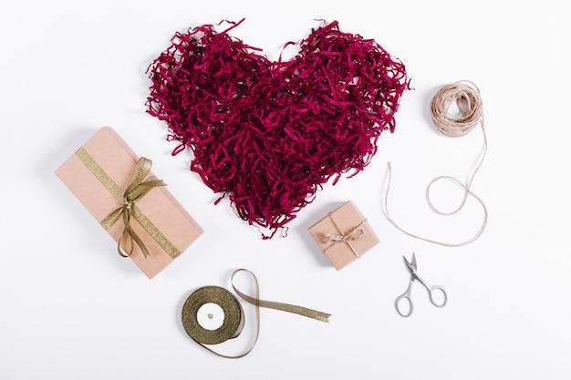 Boîtes à cadeaux avec des rubans et un coeur rouge décoratif sur un tableau blanc