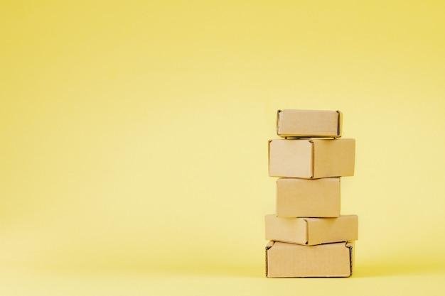 Boîtes en carton de différentes tailles sur fond jaune.