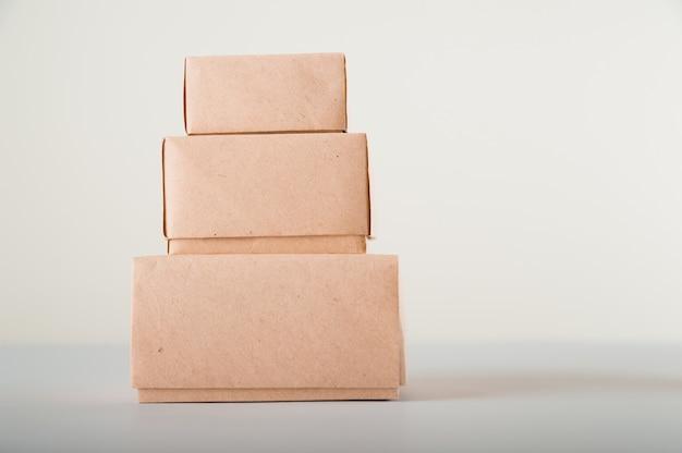 Boîtes en carton sur un espace blanc. emballage écologique des produits en papier gros plan et espace de copie. conteneurs artisanaux, emballages, boîtes, colis.