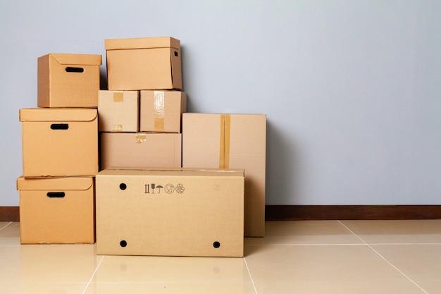 Boîtes en carton pour se déplacer sur le sol contre un mur gris