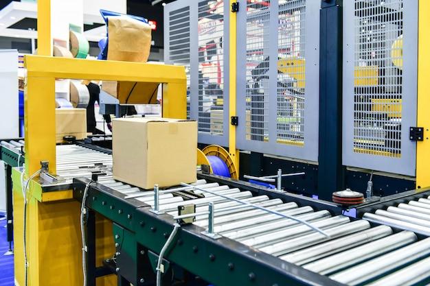 Boîtes en carton sur tapis roulant dans un entrepôt de distribution