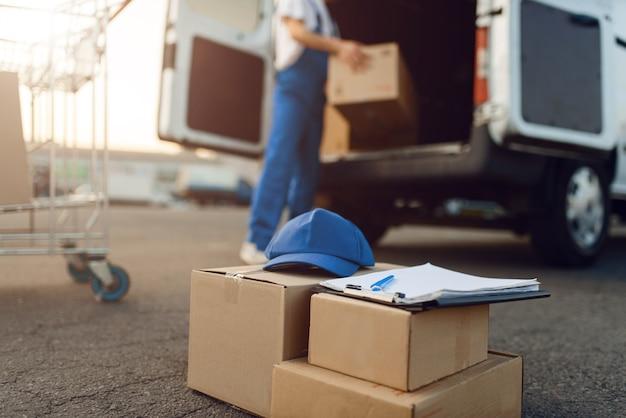 Boîtes à colis et bouchon, livreur, service de livraison. homme debout à des colis en carton dans un véhicule, un homme livrer, un courrier ou un travail d'expédition