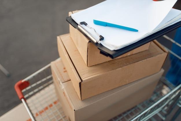 Boîtes à colis et cahier dans un chariot de fret, concept de service de livraison, entreprise de livraison, personne. colis en carton, livraison, coursier ou expédition