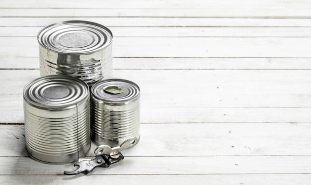 Boîtes de conserve avec de la nourriture et un ouvre-porte. sur une table en bois blanche.