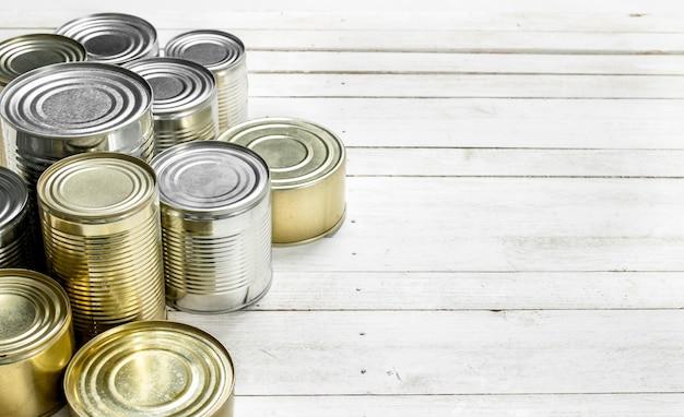Boîtes de conserve avec de la nourriture sur une table en bois blanc