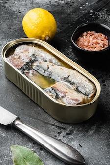 Boîtes de conserves de sardines, sur fond de table en pierre noire noire