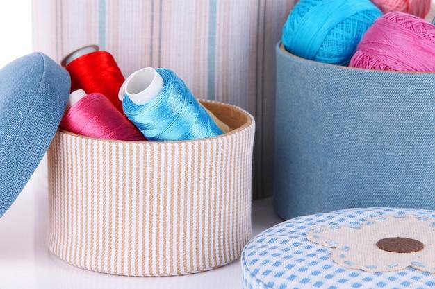 Boîtes décoratives avec des écheveaux colorés de fil close up