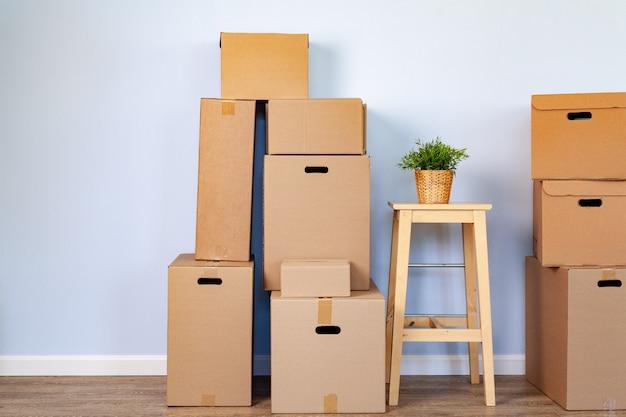 Boîtes de déménagement avec trucs emballés et chaise pour le déménagement