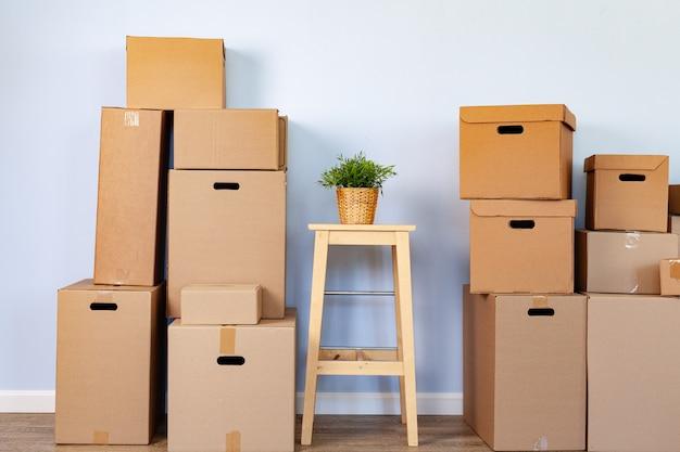 Boîtes de déménagement avec trucs emballés et chaise pour se déplacer