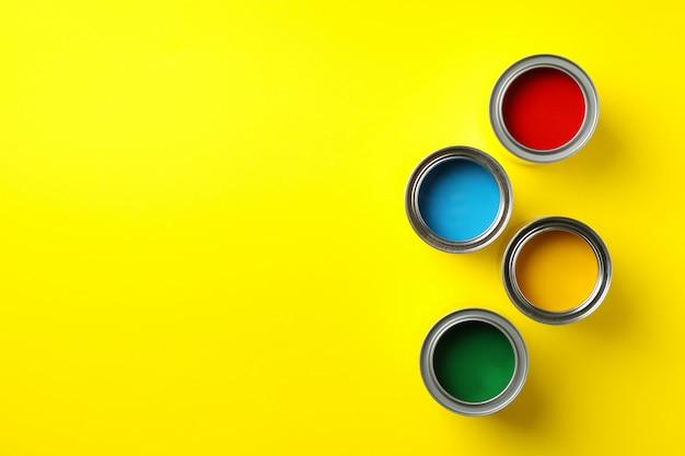 Boîtes de différentes peintures sur fond jaune, vue de dessus