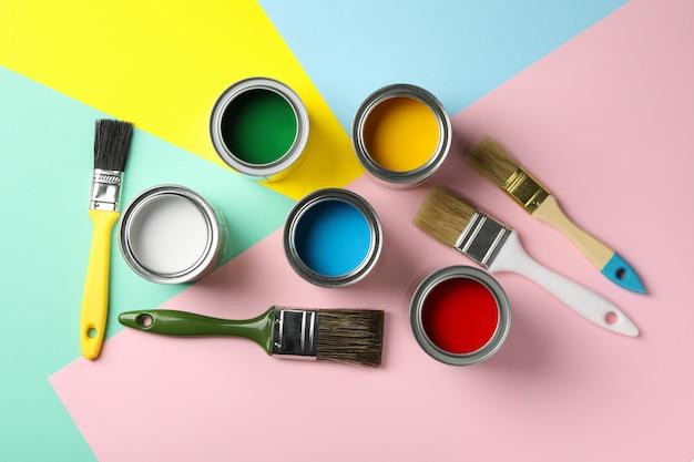 Boîtes avec différentes peintures et pinceaux sur fond multicolore, vue de dessus