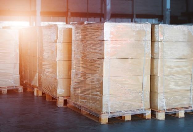 Boîtes d'emballage film plastique enveloppé sur des palettes dans un entrepôt de stockage entrepôt d'expédition de fret