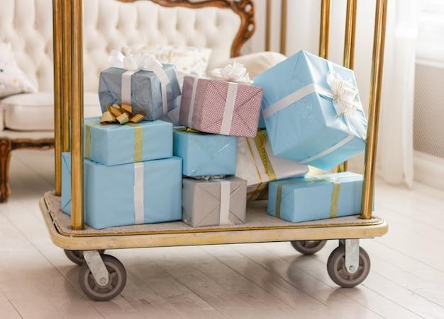 Boîtes emballées avec des cadeaux de noël sur un chariot de nombreux cadeaux du nouvel an