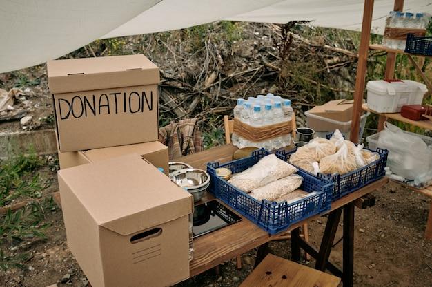 Boîtes emballées avec des vêtements et des dons de nourriture sur la table