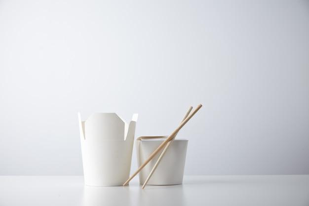 Boîtes à emporter ouvertes et fermées pour nouilles chinoises présentées avec des baguettes