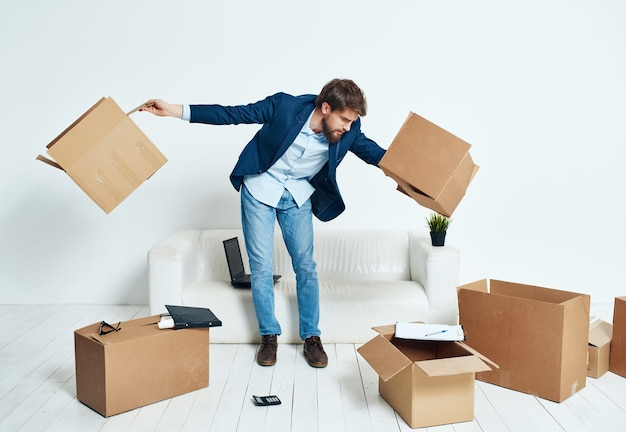 Boîtes d'homme d'affaires avec des choses se déplaçant vers un nouveau lieu de travail déballage