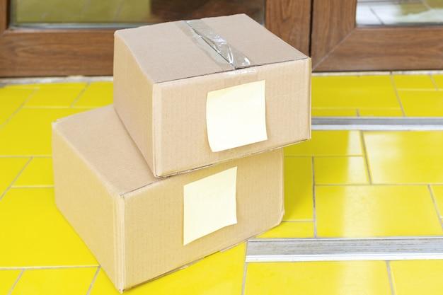 Boîtes de livraison sur le pas de la porte près de la maison. livraison de nourriture sans contact. achats en toute sécurité e-commerce acheter des colis à la maison. boîtes livrées à la porte d'entrée par courrier, facteur