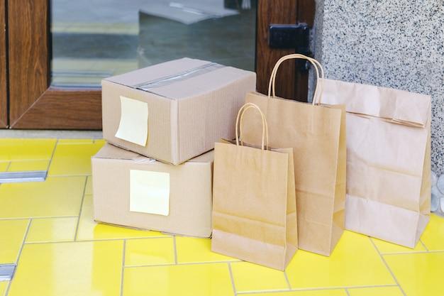 Boîtes de livraison, sacs en papier sur le pas de la porte près de la porte de la maison. livraison de nourriture sans contact. achats en toute sécurité e-commerce acheter des colis à domicile. boîtes livrées à la porte d'entrée par courrier, facteur.
