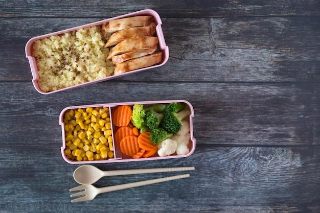 Boîtes à lunch à l'école avec poulet, bouillie, légumes frais sur fond de bois foncé. vue de dessus. place pour le texte