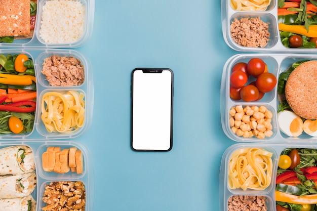 Boîtes à lunch vue de dessus avec téléphone vierge