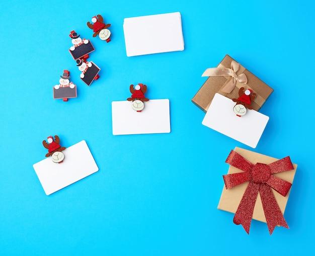 Boîtes avec noeuds rouges, cartes de visite blanches vierges et pinces à linge décoratives