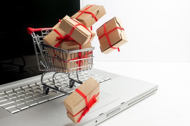 Boîtes en papier dans un panier sur un clavier d'ordinateur portable. idées sur le commerce électronique, une transaction d'achat ou de vente de biens ou de services en ligne.