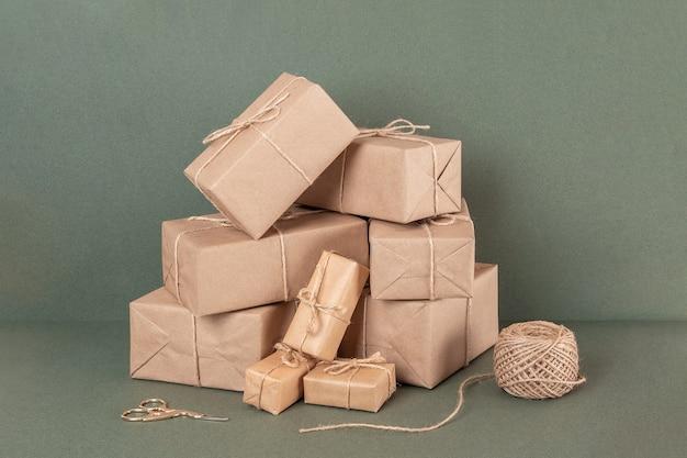 Boîtes en papier kraft, ficelle et ciseaux sur fond vert. concept vacances de noël ou du nouvel an, zéro déchet joyeux noël. vue de face.