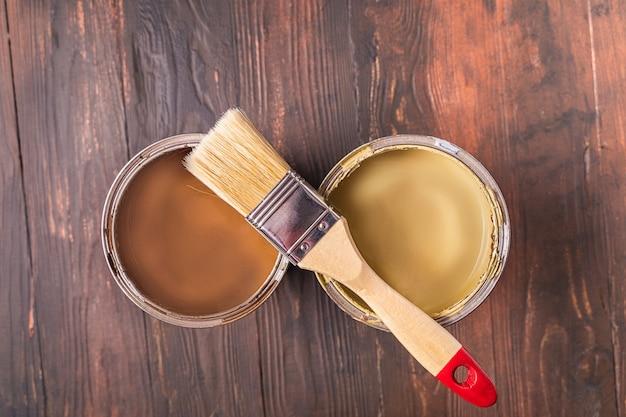 Boîtes de peinture de couleur marron clair et foncé sur fond de bois. copiez l'espace pour le texte. mise à plat style rustique.