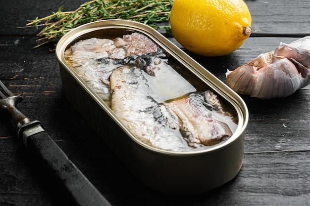 Boîtes de sardines de conserves, sur fond de table en bois noir