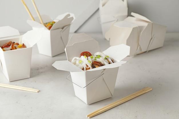 Boîtes avec de savoureuses nouilles de riz isolés