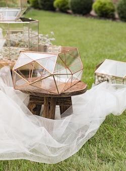 Boîtes en verre de mariage pour enveloppes pour salutations sur petite table en bois et tissu blanc avec des plantes comme décoration