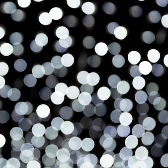 Bokeh abstrait des lumières de la ville blanches sur fond noir. défocalisé et flouté de nombreuses lumières rondes.