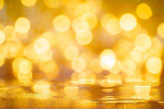 Bokeh doré doux, doux et chatoyant. éléments lumineux changeants riches et chauds sur fond doré. un effet magique. un peu comme de l'eau ondulante.