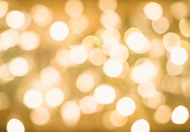 Bokeh floue fond rougeoyant de noël doré. lumières de noël. résumé historique de vacances or nouvel an abstrait paillettes sans mise au point avec des étoiles clignotantes et des étincelles.