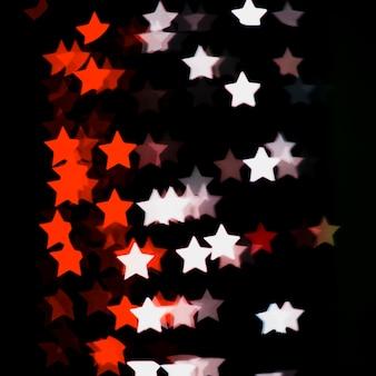 Bokeh fond avec des lumières rouges et blanches en forme d'étoile