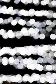 Bokeh lumières blanches sur fond noir.