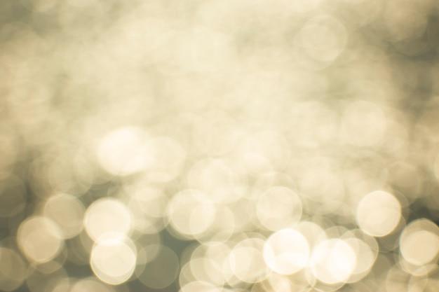 Bokeh de réflexion de lumière dorée de la surface de l'eau ondulée dans la lumière du soleil du matin