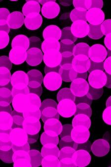 Bokeh violet abstrait flou sur fond noir.