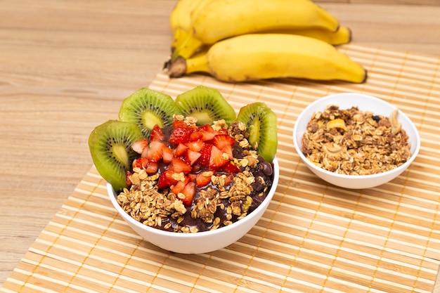 Bol d'aã§ai soverte, sur table en bois avec fraise et granola.