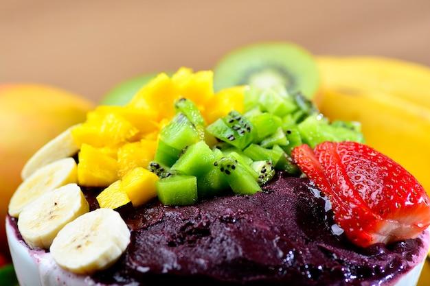 Bol acai avec salade de fruits banane mangue kiwi et fraise